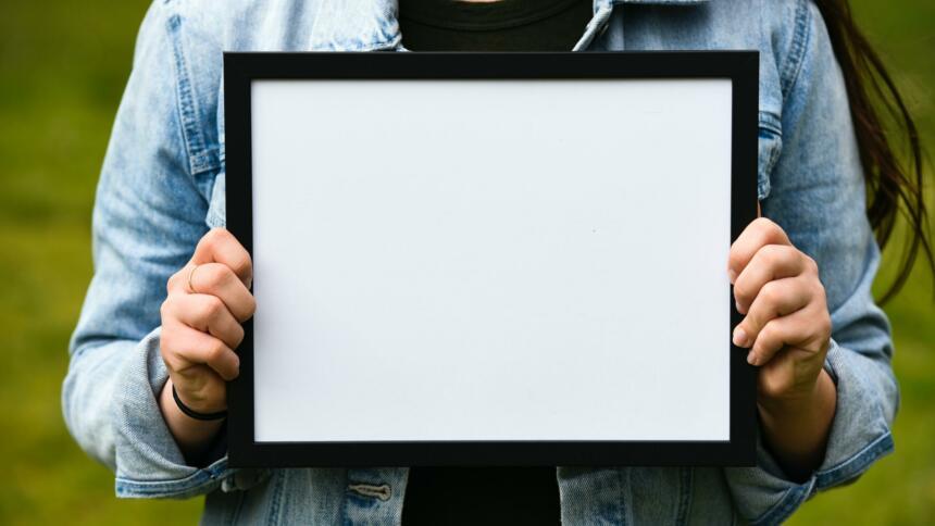 Person hält ein schwarz eingerahmtes weißes Blatt hoch