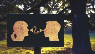"""Schild mit Silhouetten von zwei Köpfen und """"2m""""-Aufschrift"""
