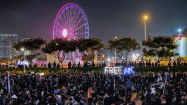 """Demonstration mit Leuchtschrift """"Free HK"""", im Hintergrund ein beleuchtetes Riesenrad"""
