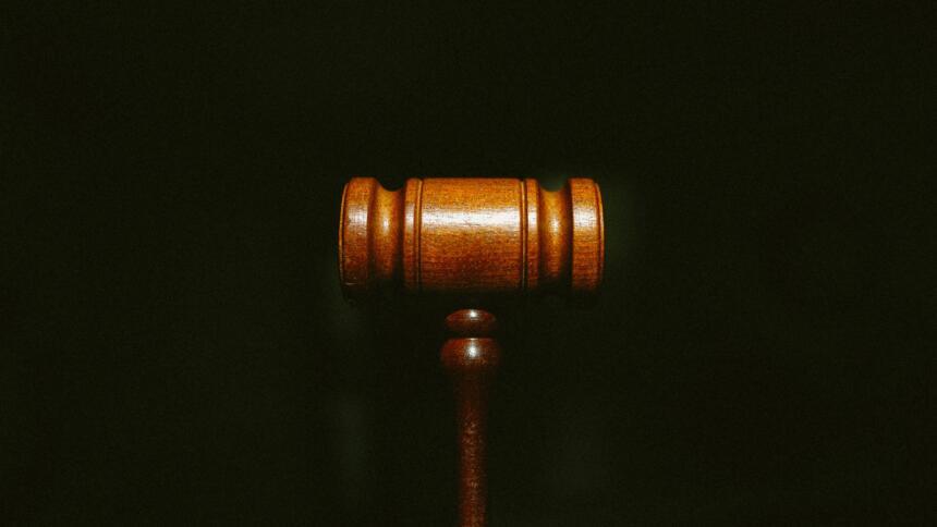 Ein Richter:innen-Hammer auf schwarzem Hintergrund