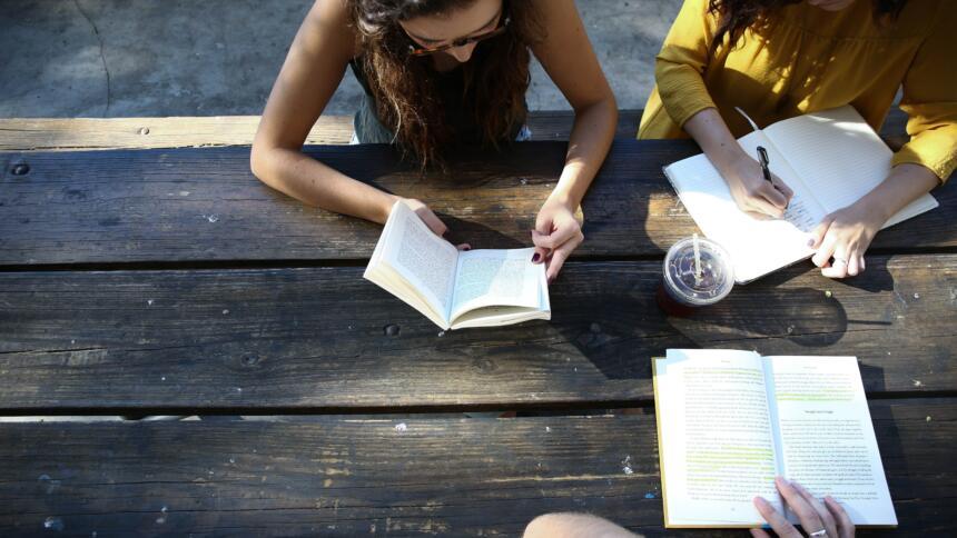 Eine Frau sitzt mit einem Buch an einem Tisch