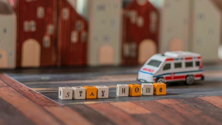 """Spielzeug-Krankenwagen fährt an Häuser und dem Schriftzug """"Stay home"""" auf Bauklötzchen vorbei."""