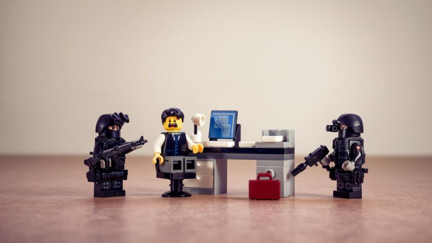 Zwei Lego-Polizisten umringen einen Lego-Behördenmitarbeiter, der ängstlich schaut.