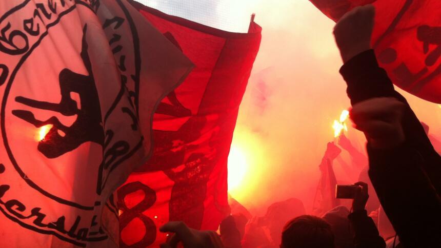 Fans des 1. FC Kaiserslautern mit Pyrotechnik, Fahnen und gereckten Fäusten.