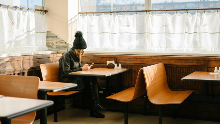 Person sitzt in einem leeren Restaurant und schaut auf Handy