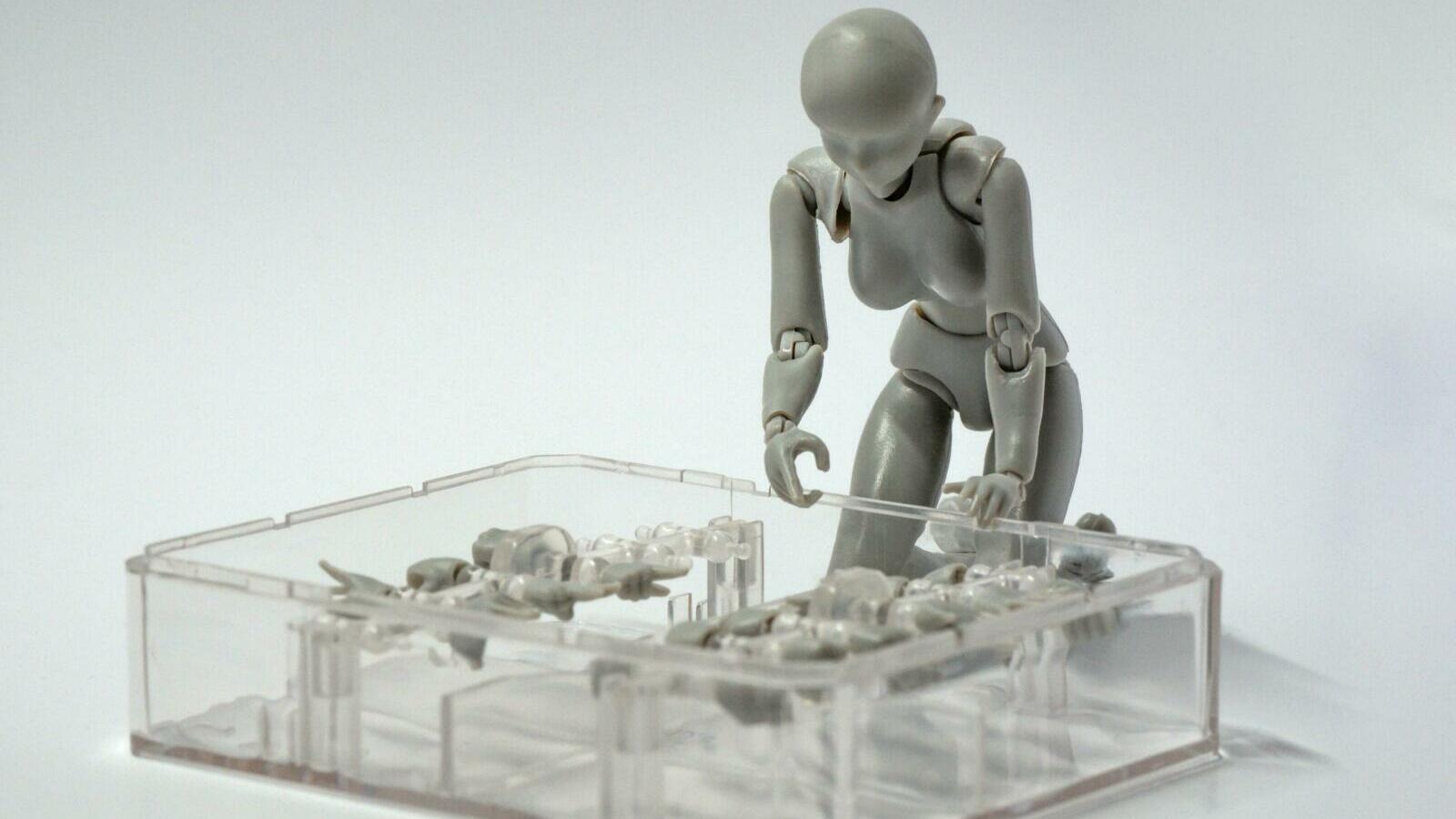 Roboter vor einem Kasten mit Roboterteilen.