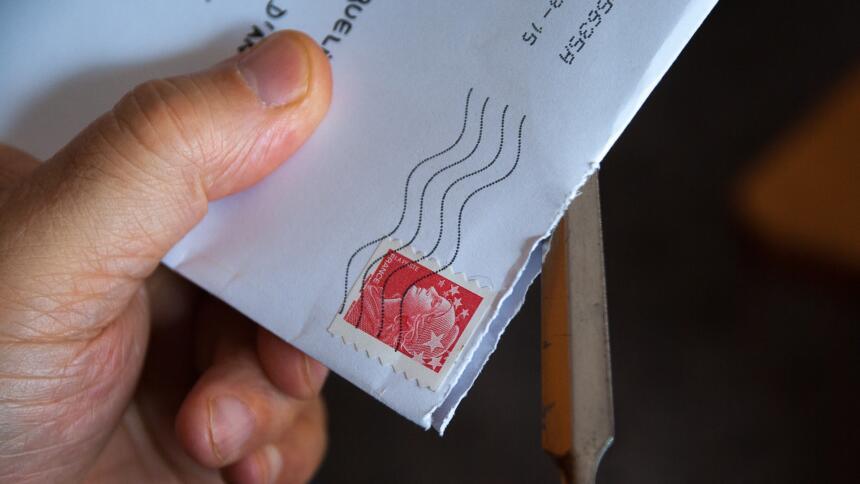 Jemand öffnet mit einem Brieföffner einen Brief