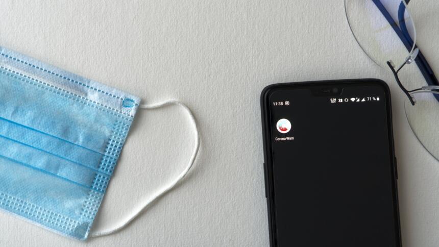 Maske, Handy mit Corona-Warn-App und Brille liegen auf einem Tisch