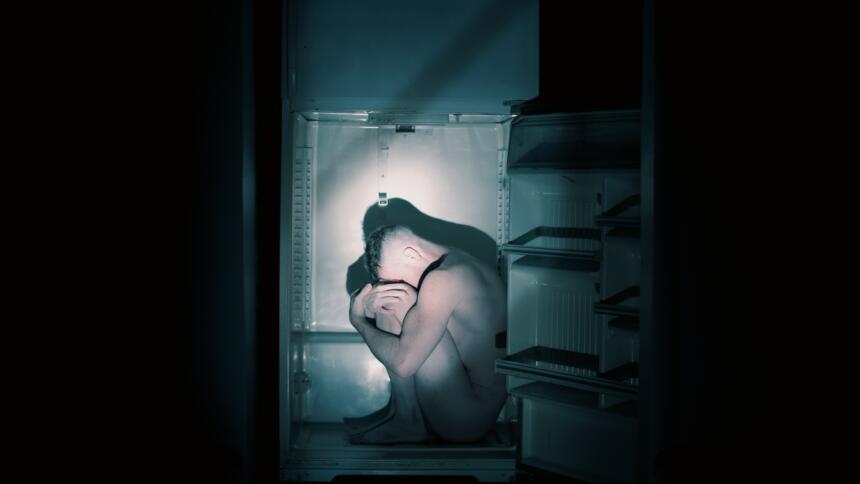 Nackter Mensch sitzt in einem Kühlschrank