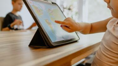 Ein Kind tippt auf eine weltkarte, die auf einem Tablet abgebildet ist