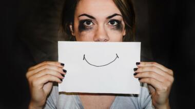 Ein Smiley auf Papier vor einem traurigen Augenpaar