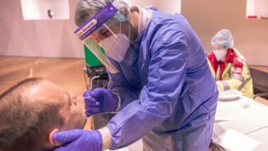 Medizinisches Personal in Schutzkleidung nimmt bei einem Patienten einen Nasenabstrich.