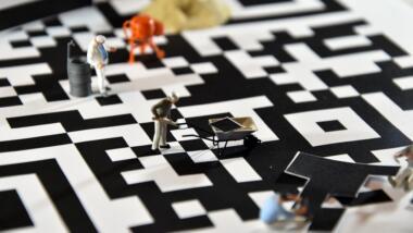 Spielzeugfiguren mit Schubkarre und Betonmischer bauen einen übergroßen QR-Code zusammen.
