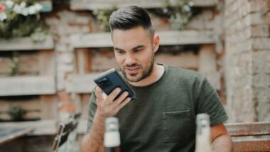 Mann sitzt im Biergarten und schaut aufs Handy