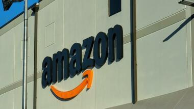 Graues Gebäude mit Amazon Schriftzug vor blauem Himmel
