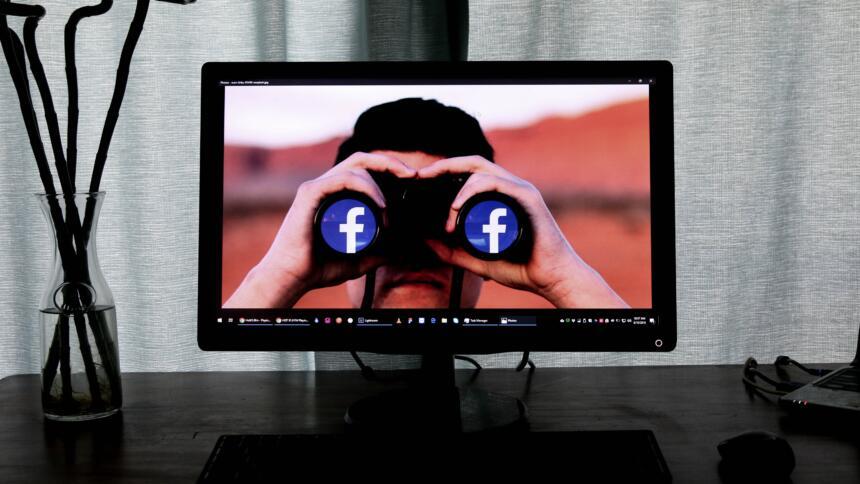 Mann guckt durch Fernglas mit Facebook Logo