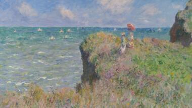 Zwei Menschen stehen an der Klippe am Meer bei schönsten Frühlingswetter.