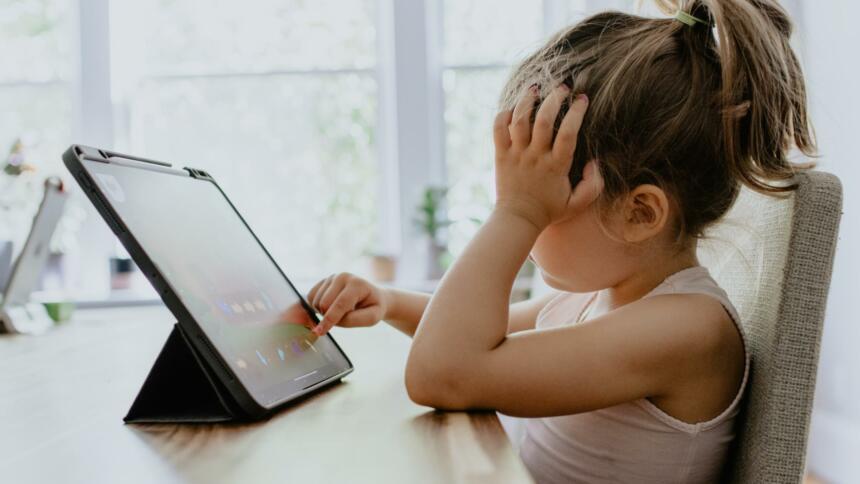 Ein Kind sitzt an einem Tablet und stützt den Kopf ab
