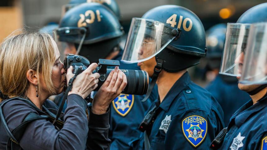 Fotografin mit Teleobjektiv vor einer Polizeikette