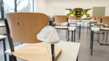 Klassenzimmer mit Maske und Baden-Württemberg-Logo