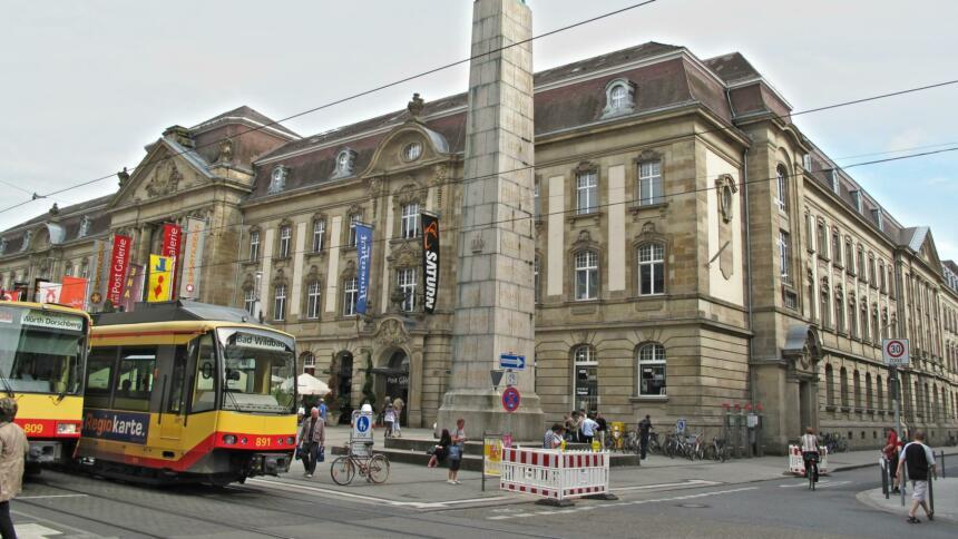 Postgalerie am Europaplatz Karlsruhe. Im Vordergrund Straßenbahnen und Passant:innen.