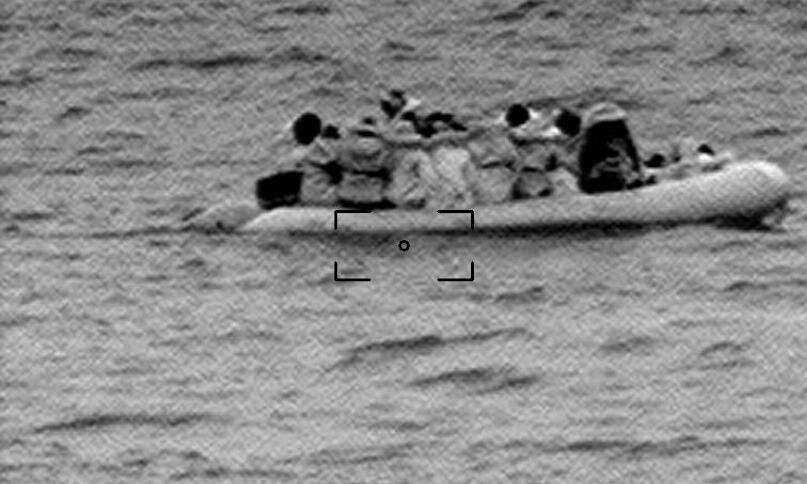 Das körnige Bild zeigt ein Boot mit Geflüchteten.