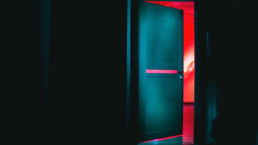 Geöffnete Tür in dunklem Raum