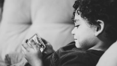 Kind schaut auf Smartphone