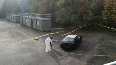 Das Foto zeigt ein Fahrzeug mit Tatortspuren und Ermittler:innen in weißen Anzügen.