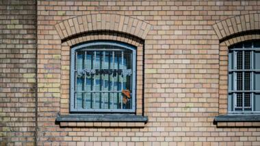 In einem vergitterten Fenster hängen Socken