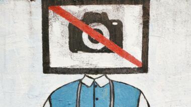 Graffiti mit durchgestrichener Kamera vor dem Kopf einer Person