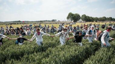 Menschen ziehen bei einem Protest über Felder