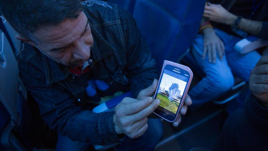 Ein Mann zeigt Bilder seiner Heimatstadt auf dem Smartphone
