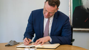 Jens Spahn sitzt an einem Tisch und schreibt in ein Buch.