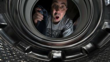 Mensch schaut in eine Waschmaschinentrommel