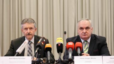 Zwei weiße Männer in dunklen Anzügen blicken grimmig.