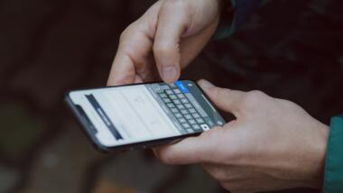 Ein Mensch hält ein Smartphone.