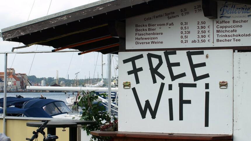 Eine kleine Kneipe in einer Holzhütte an einem Hafen. Die Hütte ist mit Brettern vernagelt. Auf einem steht Free WiFi.