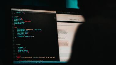 Eine Person sitzt in einem dunklen Raum vor einem Bildschirm und betrachtet einen HTML-Code.