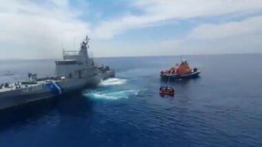 Das Bild zeigt zwei Schiffe der griechischen Küstenwache, von denen eines eine Rettungsinsel an einem Seil hinter sich herzieht.
