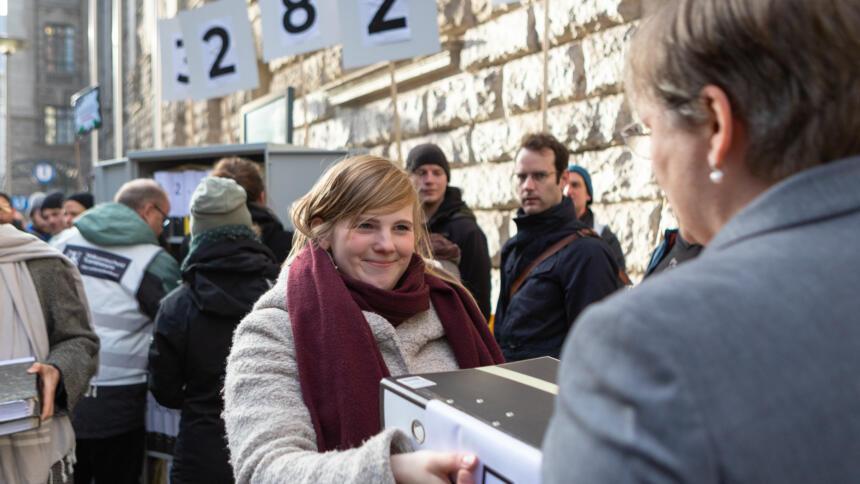 Eine Frau übergibt vor einem großen Gebäude in Berlin mehrere Aktenordner.