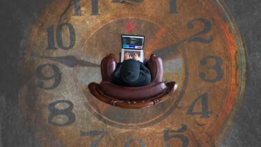Mensch mit Laptop von oben fotografiert, der in einer auf den Boden gemalten Uhr sitzt