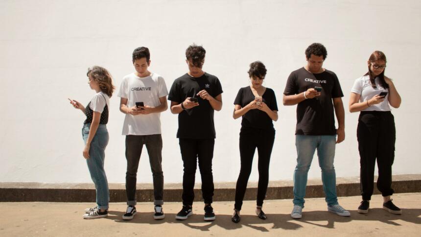 Sechs junge Menschen stehen in einer Reihe, alle schauen auf ihr Smartphone.