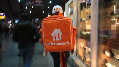 Eine Person mit großem, oragenen Lieferandorucksack im Frankfurter Hauptbahnhof
