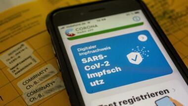 Smartphone mit digitalem Impfnachweis in der Corona-Warn-App liegt auf einem gelben Impfpass mit Comirnaty-Aufklebern.