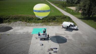 """Das Bild zeigt einen gelben Heliumballon mit der Aufschrift """"Polizei"""" sowie einen Anhänger und ein Begleitfahrzeug."""