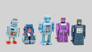 Fünf kleine bunte Spielzeugroboter stehen nebeneinander.