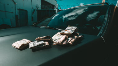 Geldbündel liegen auf der Haube eines schwarzen Autos.