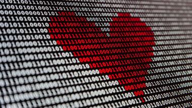 Ein rotes Herz aus Nullen und Einsen erscheint auf einem Bildschirm.