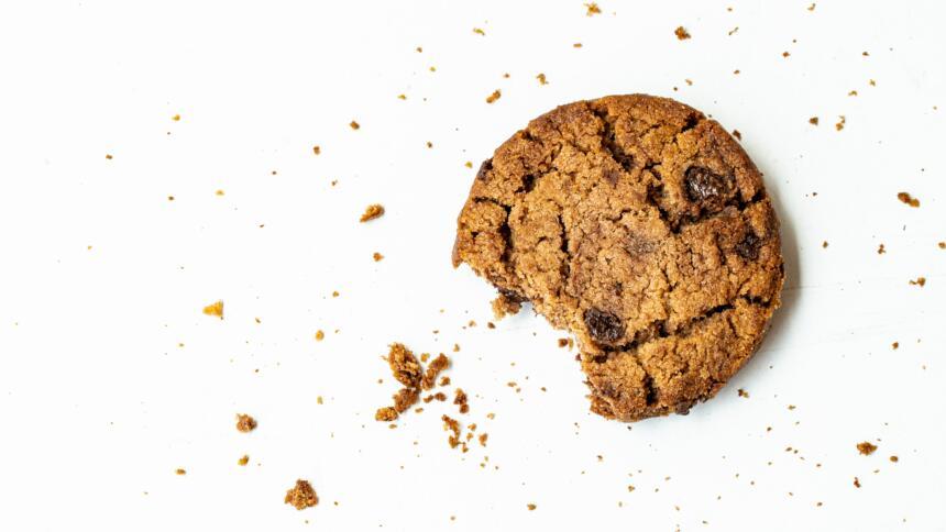 """Ein angebissener """"american-style"""" Cookie auf weissem Grund."""